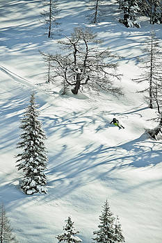 Young Male Freerider Skiing Down A Powder Slope by Leander Nardin