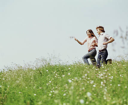 1970s Boy Girl Running Field by Vintage Images