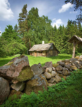 A house with stone fence on the yard by Anna Grigorjeva