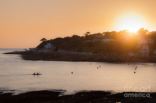 A two man canoe enters the bay at Conche de Saint Palais as the  by Peter Noyce