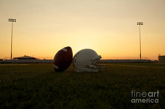 American Football and Helmet on the Field at Sunset by David Lee