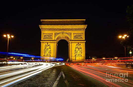 Oscar Gutierrez - Arc de Triomphe at night with streaking car lights