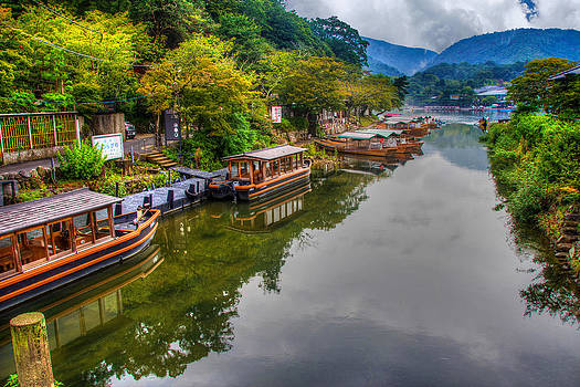 Asian pleasure boats wait on the river Hozu in Japan by Laura Palmer