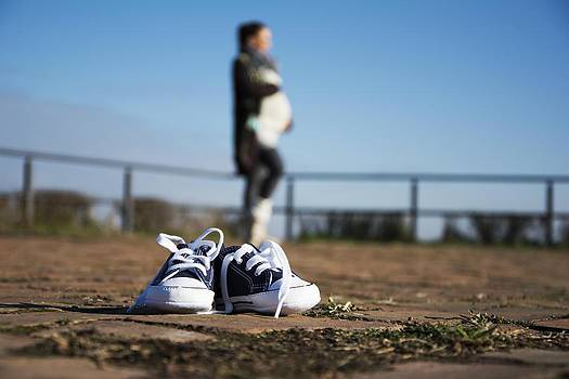 Newnow Photography By Vera Cepic - Baby shoes close up with pregnant woman behind in a blur