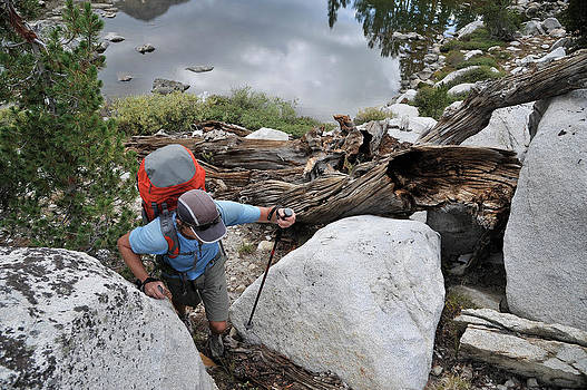 Backpacker Hiking Across Lake Basin by HagePhoto