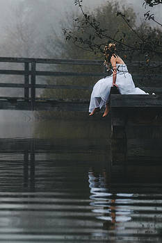 Barefoot Bride In White Wedding Dress Sitting On A Jetty At A La by Leander Nardin