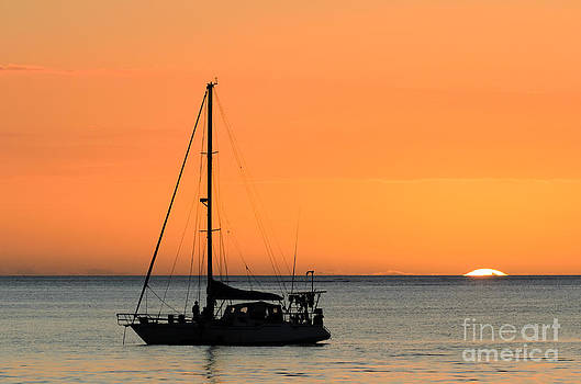 Beautiful tropical sunset over the ocean with yacht by David Hill