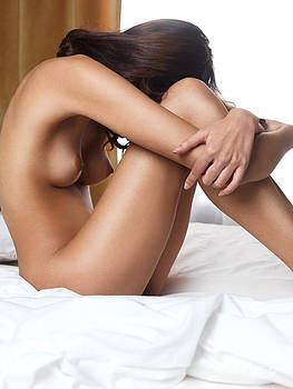 Beautiful woman sitting naked on bed with arms around her knees by Oleksiy Maksymenko