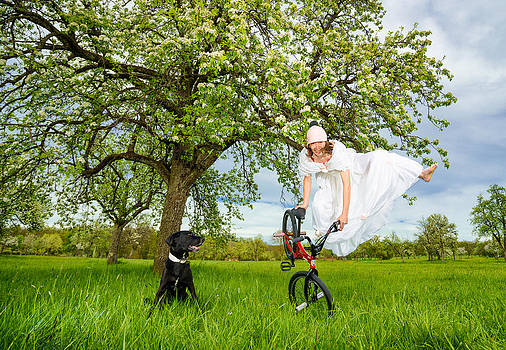 BMX Flatland Bride jumps in spring meadow by Matthias Hauser