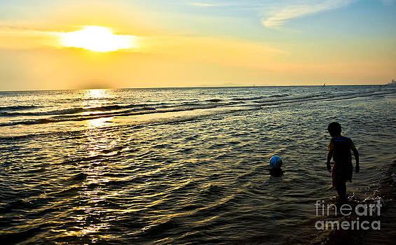 Boys Playing During Sunset At Beach by Jeng Suntorn niamwhan