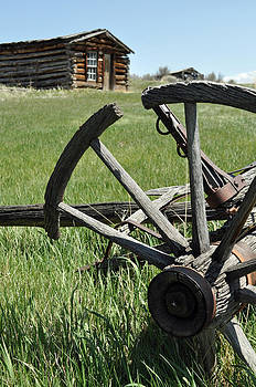 Broken Wagon Wheel and Log Building in Montana's Nevada City by Bruce Gourley