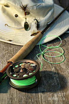 Sandra Cunningham - Close-up of fly-fishing reel and rod with hat