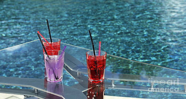Cocktail glasses on table by pool by Sami Sarkis