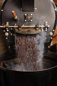 Coffee roaster pouring beans by Ron Sumners