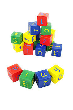 Coloured building blocks with letters on a white background by Dawn Gilfillan