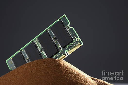 Computer memory chip on red sand by Sami Sarkis