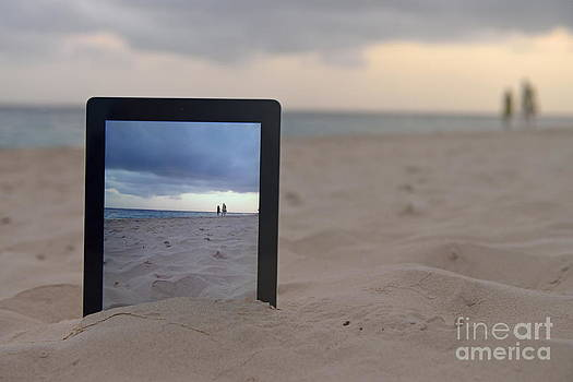 Digital tablet in sand on beach by Sami Sarkis