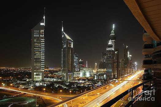 Emirates Tower and Sheik Zayed Road at Night by Juvert Ostol