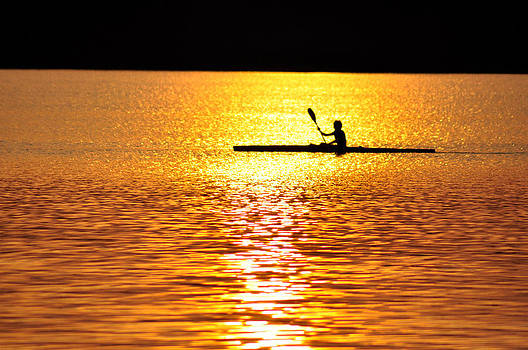 Evening paddling a kayak by Elek Gyorgy