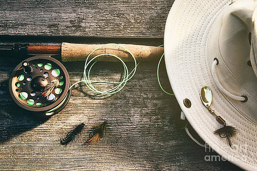 Sandra Cunningham - Fly fishing rod with hat on wood