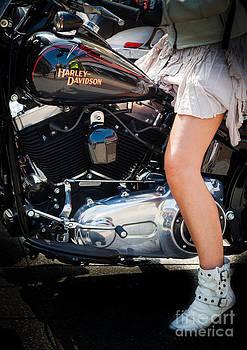Peter Noyce - girl in short skirt astride Harley Davidson v twin black motorcy