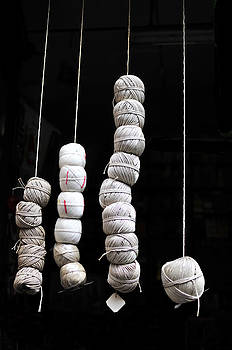 Hanging Balls of String on Black Background by Angela Bonilla
