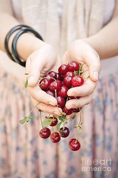 Holding cherries  by Viktor Pravdica