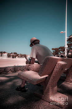 One man sitting on shady bench overlooking b by Peter Noyce