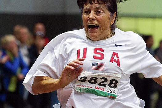 Joyful Older Female Athlete Running by Alex Rotas