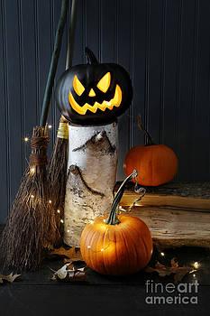 Sandra Cunningham - Lit pumpkin on log with leaves
