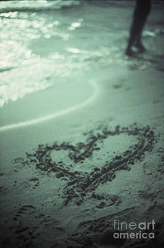 Love heart drawn on beach sand at low tide with ocean sea by Edward Olive