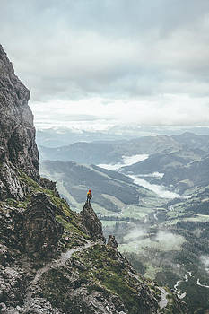 Male Mountaineer In Rugged Landscpae Standing On A Rock Overlook by Leander Nardin