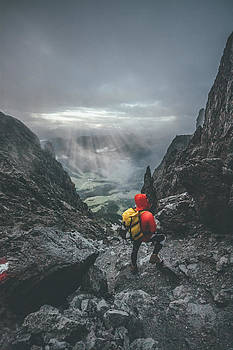 Male Mountaineer Standing In Harsh Rockformation With A Panorama by Leander Nardin