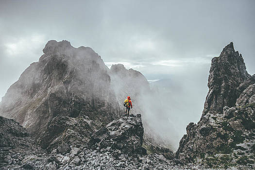 Male Mountaineer Standing On Top Of A Mountain In A Rugged Lands by Leander Nardin