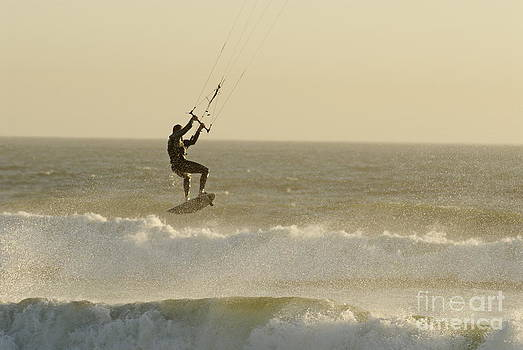 Man kitesurfing on high waves by Sami Sarkis