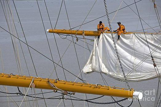 Men repairing sail of three-masted sailboat by Sami Sarkis