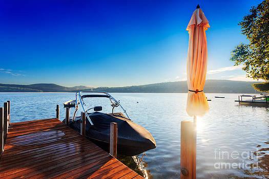 Jo Ann Snover - Morning sun behind umbrella on lakeside dock
