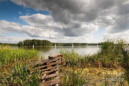 Old bridge and boats at the lake by Arletta Cwalina