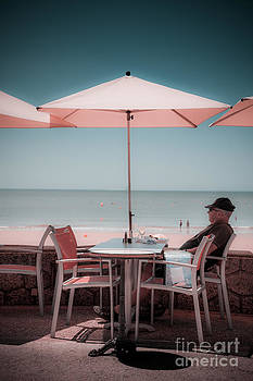One man sitting under umbrella at cafe table by beach. by Peter Noyce