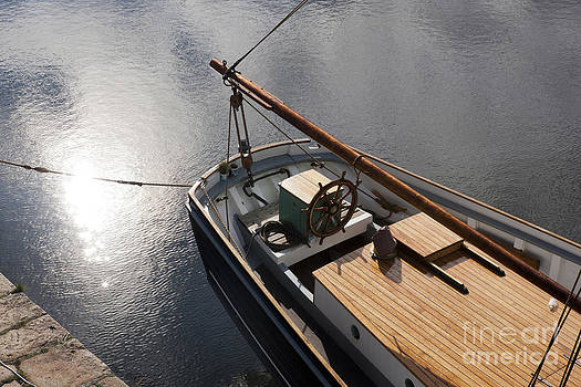 Pale autumn sunlight on the surface of water beside at tallship  by Paul Felix