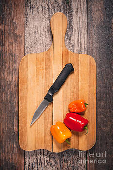 Peppers And Knife On Cutting Board by Sharon Dominick