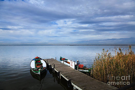 Picturesque view of jetty on Lake Albufera with boats awaiting c by Peter Noyce