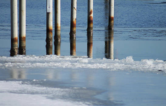 Pole reflections in the water by Danielle Allard
