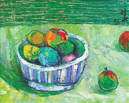 Rainbow fruit in bowl on green by Siang Hua Wang