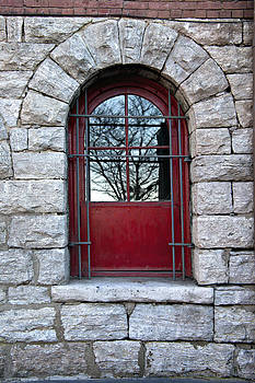 Red barred window in stone wall by Heather Reeder