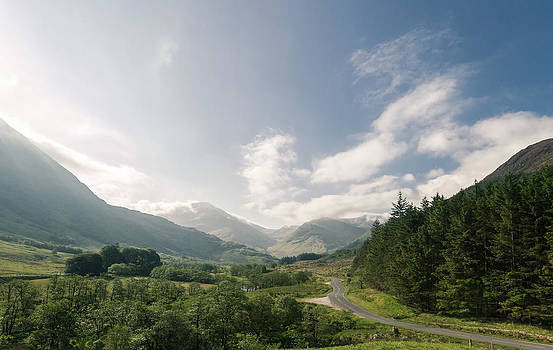 Road through a valley in the scottish highlands by Leander Nardin