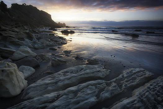 Rocky beach at dusk by Photographos ORG