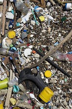 Rubbish among pebbles on beach by Sami Sarkis