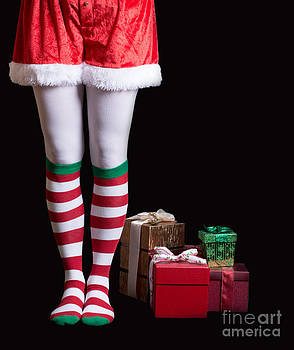 Edward Fielding - Santas Elf legs next to a pile of Christmas gifts over black