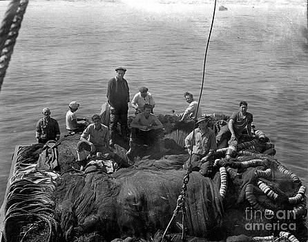 California Views Mr Pat Hathaway Archives - Sardine fishermen sitting on nets on the turn-table on the back of the boat 1930